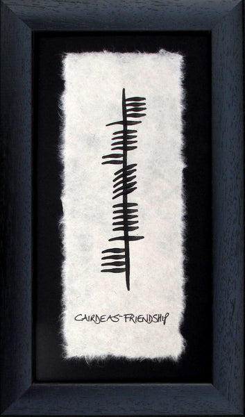 Contained in a black wooden frame is a piece of parchment with ancient Irish writing Ogham declaring friendship (cairdeas) in gaelic.  Designed and made in Ireland.