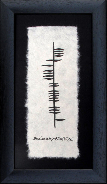 Contained in a black frame is a piece of parchment paper with ancient irish writing Ogham declaring gratitude (buíochas) in gaelic Designed and handmade in Ireland