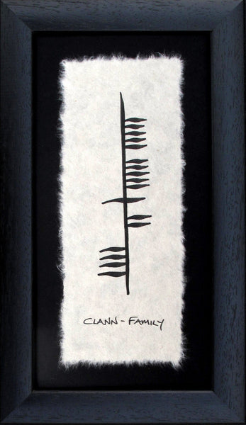 Contained in a black wooden frame is a piece of parchment with ancient Irish writing Ogham declaring family (Clann) in gaelic.  Designed and made in Ireland.
