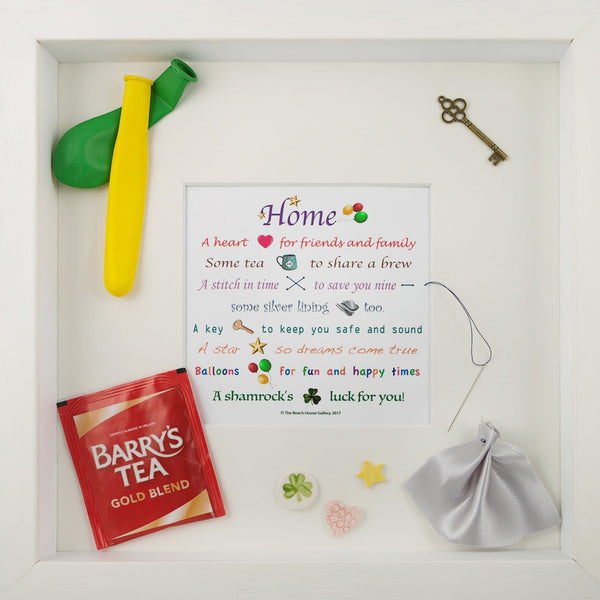 This white wooden frame, contains a poem and various small items to commemorate an event, in this case  as a house warming gift. Designed by Pippa Sweeney and made in Ireland.