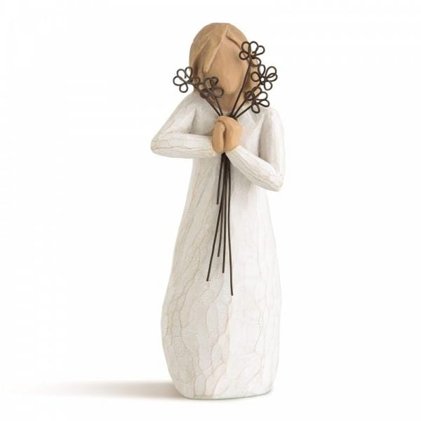 Willow tree friendship is a figurine of a girl holding flowers up to her face