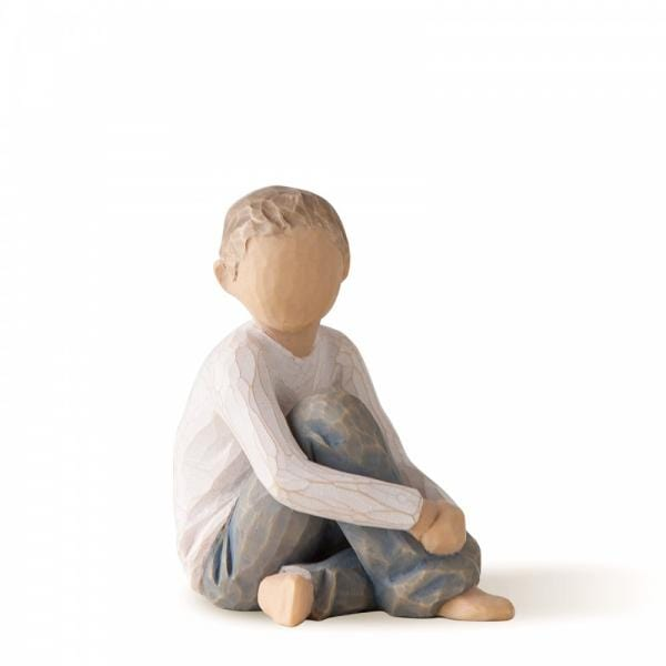 Willow Tree Caring Child is a figurine of a blond haired boy sitting with his arms around one of  knees and the other is tucked under