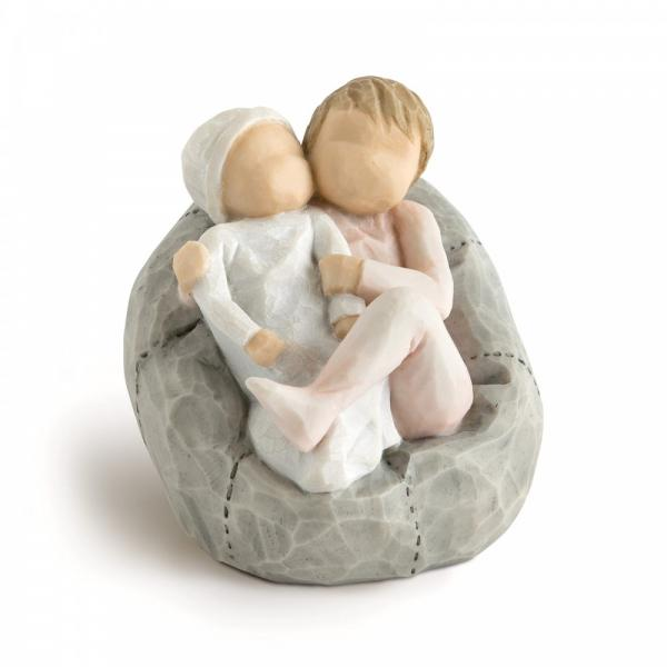 Willow tree New Baby Girl blush pink is a figurine of a small gilr and sister holding her new born brother or sister and sitting on a beanbag