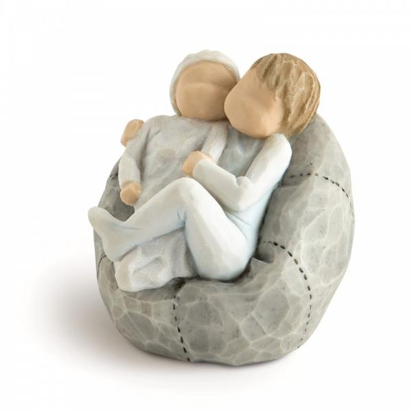 Willow tree New baby sky blue is a figurine of a brother holding his new baby brother or sister and sitting on a beanbag the young boy has on blue clothes