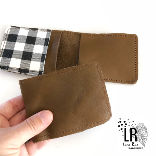 hand holding brown leather wallet, brown leather wallet with brown suede lining and black and white gingham plaid pocket on left side.