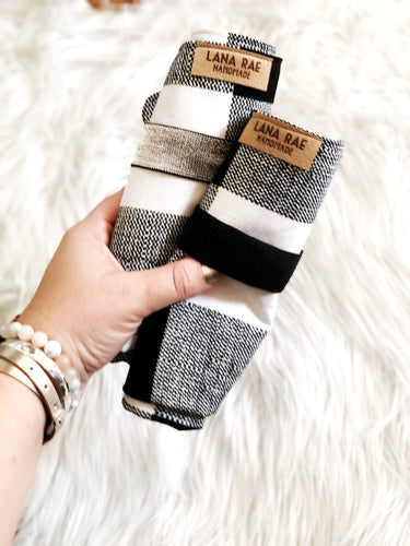 hand holding two black white buffalo plaid changing mats, rolled, leather tag on op, silver and black elastic wrapped around.