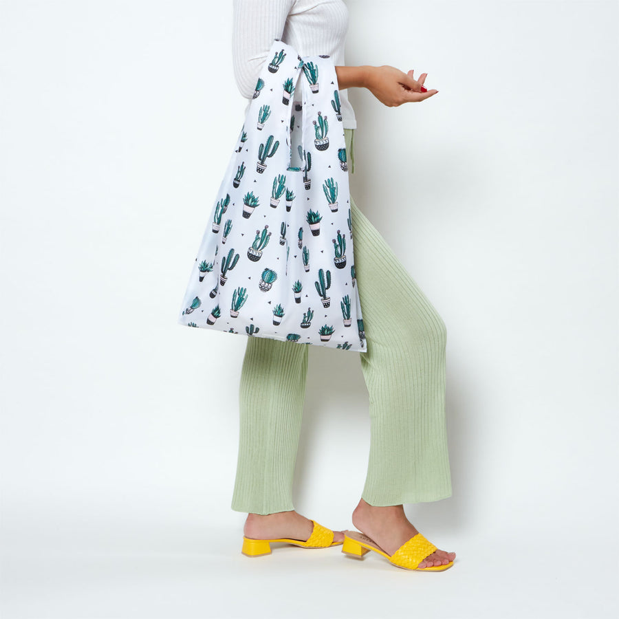 Model holding white reusable shopping bag with green plant design