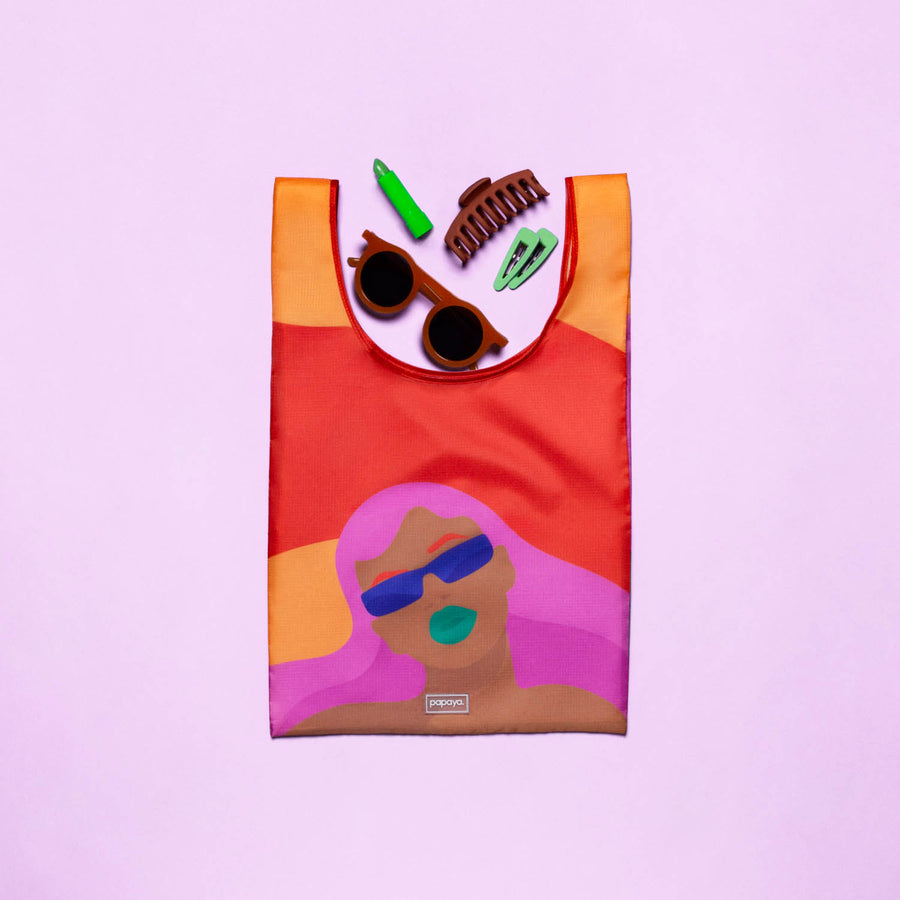 Reusable shopping bag with pink haired woman design filled with sunglasses, lipstick and hair clips