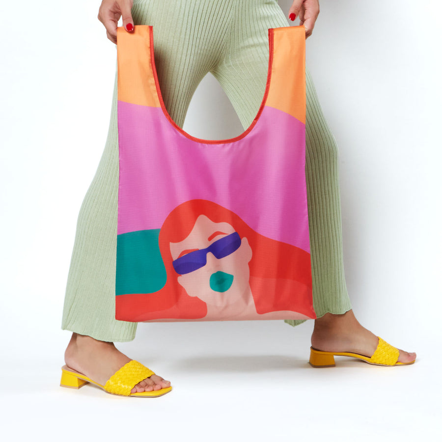 Model holding reusable shopping bag with colorful pink and red woman design by artist Laci Jordan