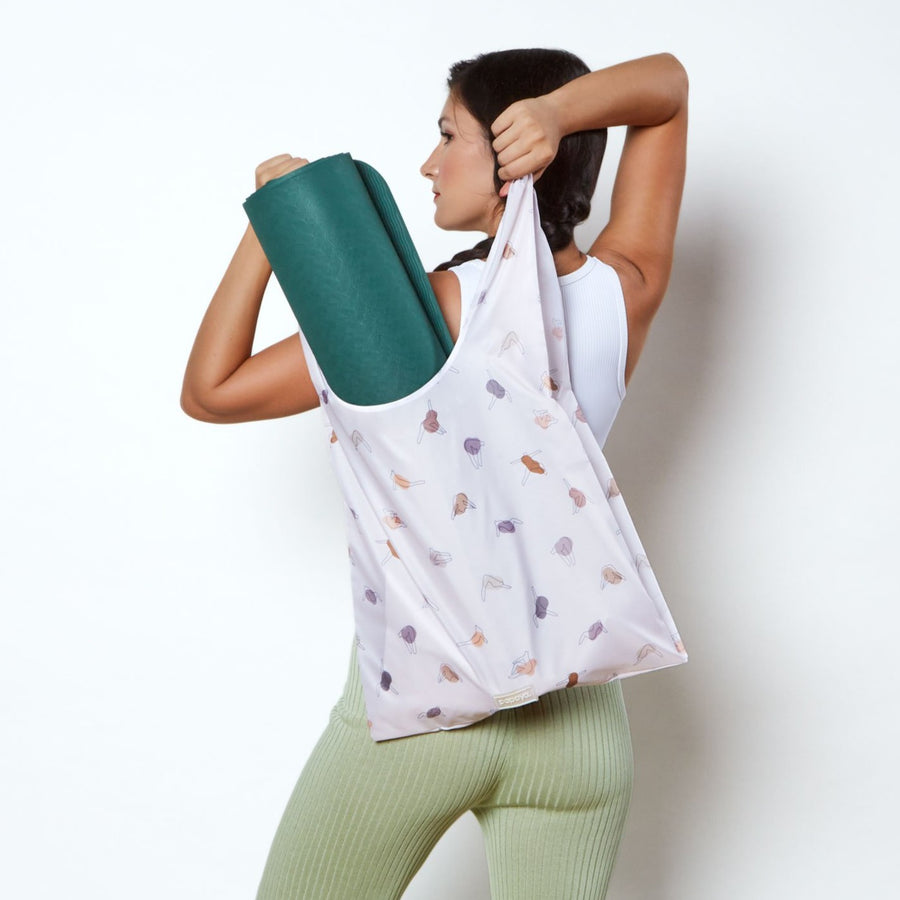 Model holding a yoga design reusable shopping bag with a yoga mat inside