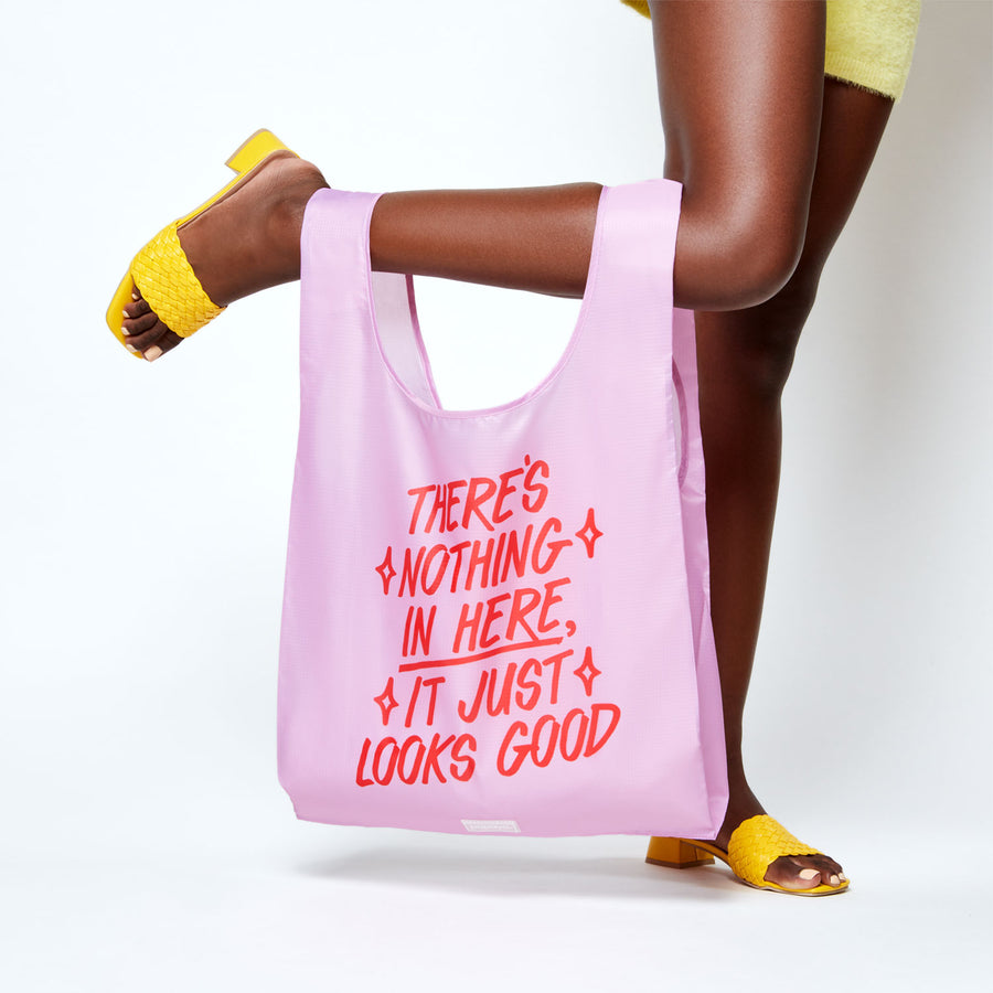 Reusable shopping bag that says There's Nothing in Here It Just Looks Good hanging on model's popped foot