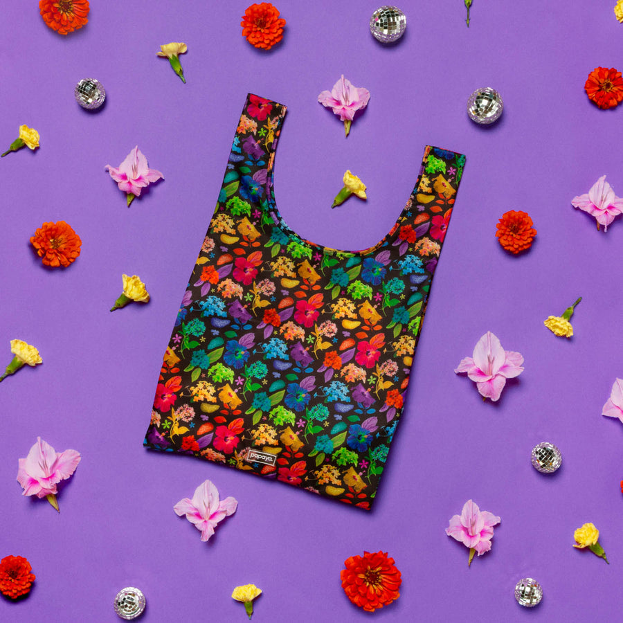 Reusable shopping bag with bright floral design surrounded by pink yellow and red flowers and disco balls