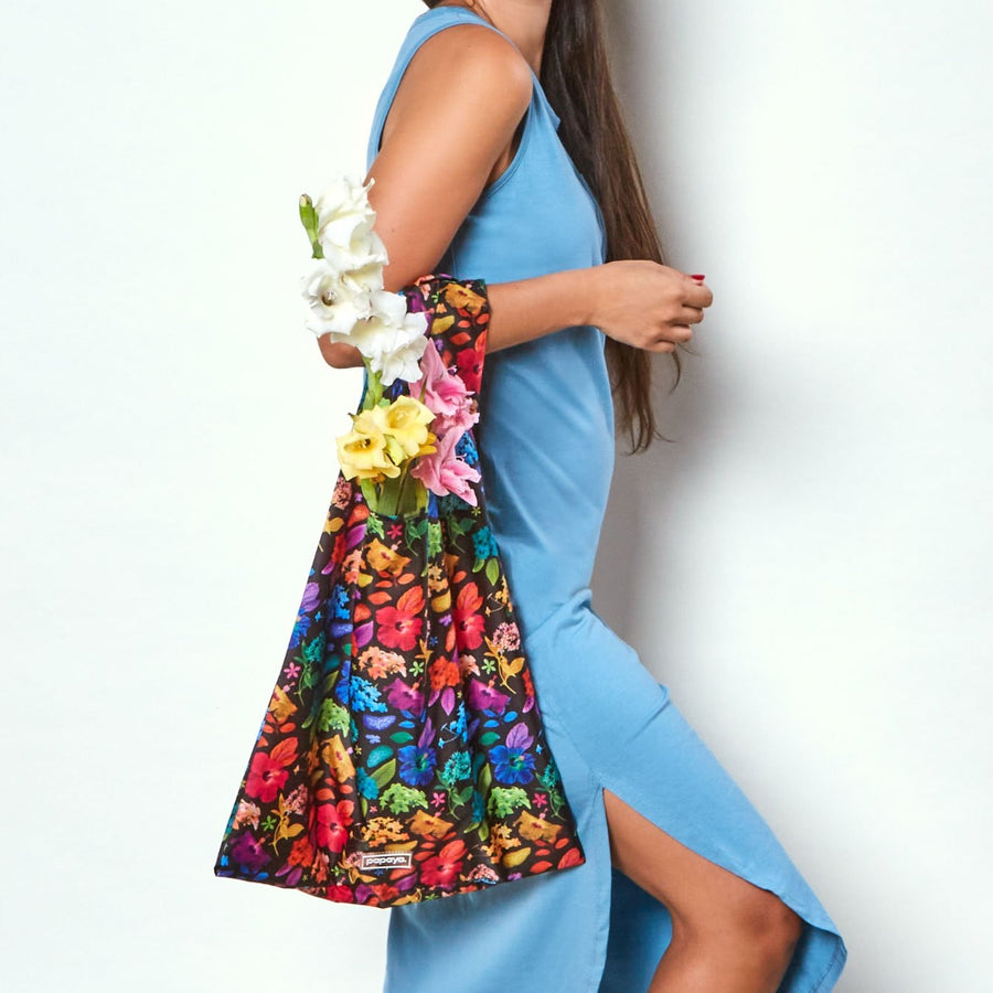 Model holding black reusable shopping bag with bright colorful floral design by artist Ramzy Masri