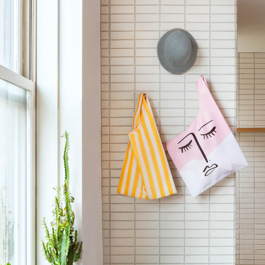Two reusable shopping bags hanging on a tiled wall with yellow stripe design and trendy line drawing of a face