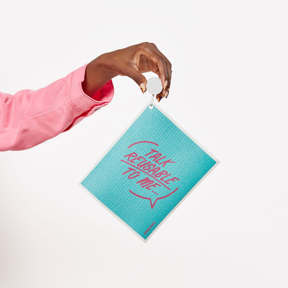 Model holding a reusable paper towel on a hook that says talk reusable to me in bright blue and pink