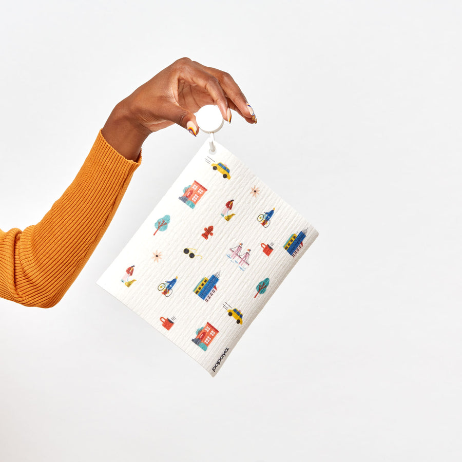 Model holding a hook with a reusable paper towel hanging on it with a city pattern design
