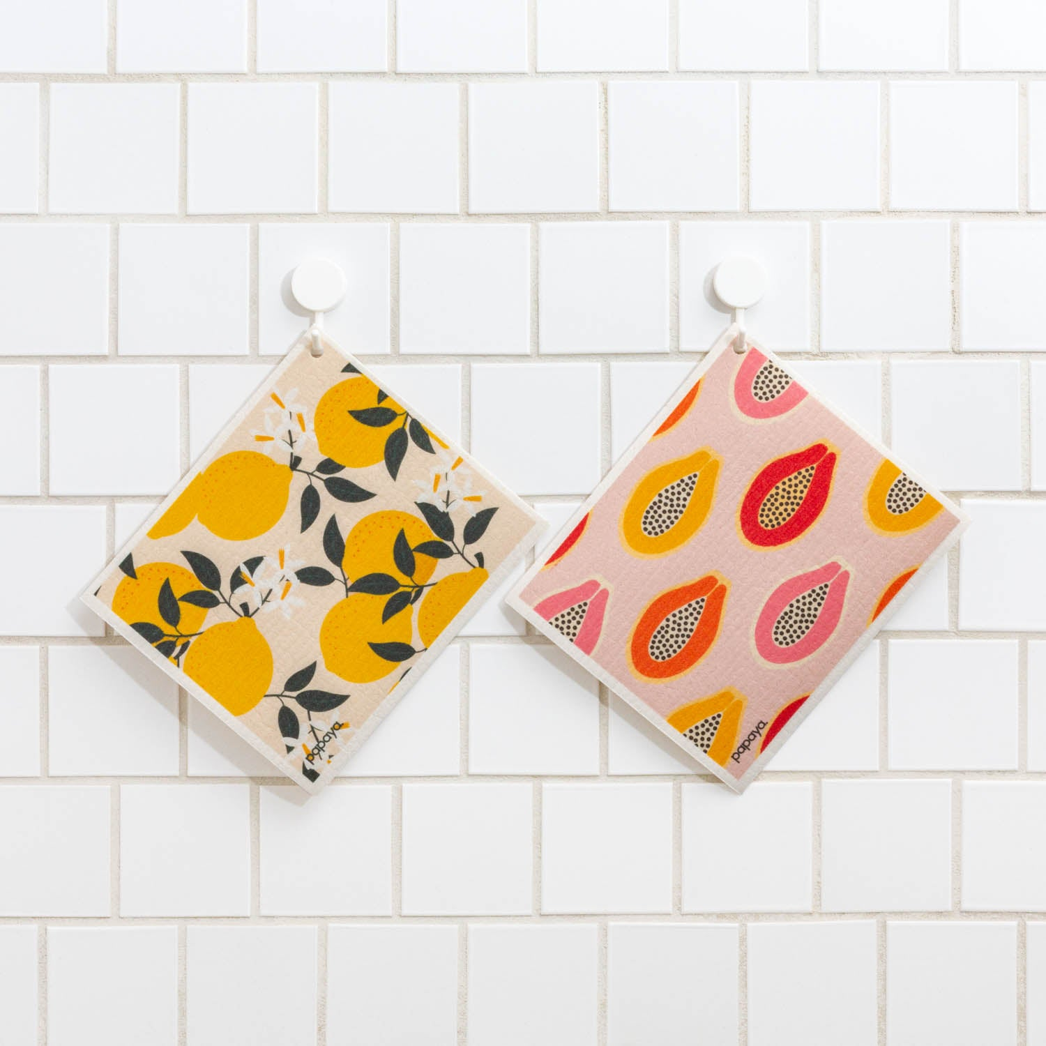 Two reusable paper towels hanging on white tile with cute and colorful lemons and papaya designs