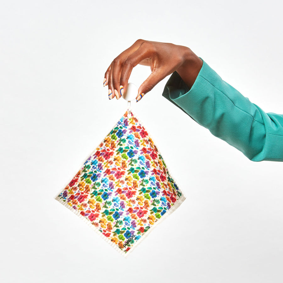 Model holding reusable paper towel hanging on a hook with colorful floral design by artist Ramzy Masri