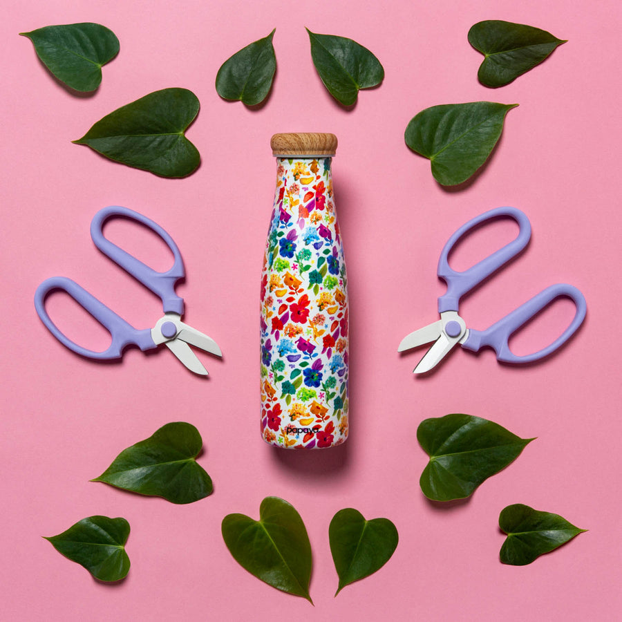 Reusable water bottle with bright and colorful flower design surrounded by scattered leaves and gardening scissors