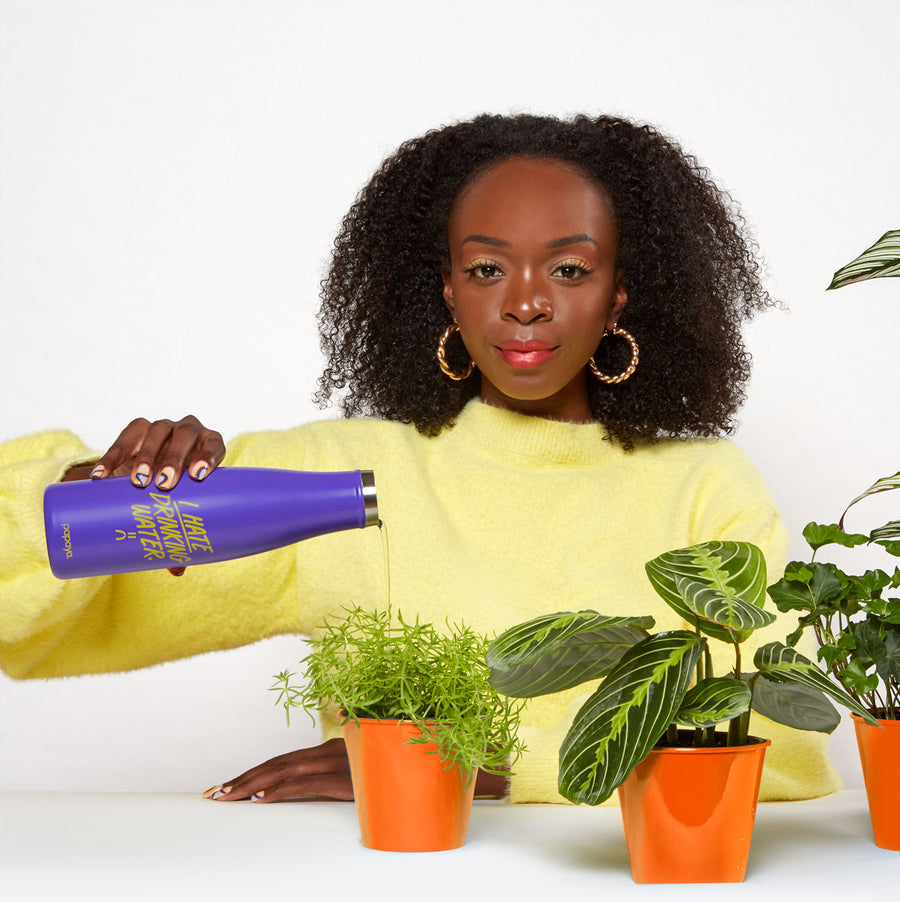 Model holding reusable stainless steel water bottle that says I hate drinking water and pouring water onto small potted plant
