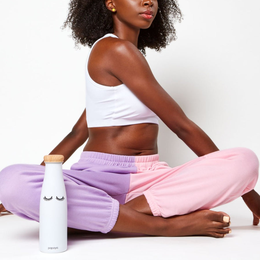 Model doing yoga pose next to reusable stainless steel water bottle in white with cute eyelashes design