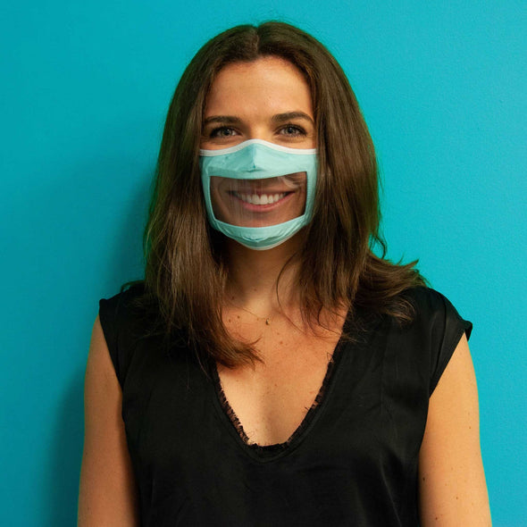 Photo of woman standing against blue background wearing Rafi Nova Adult Smile Mask in light blue with white tie behind ear loops.