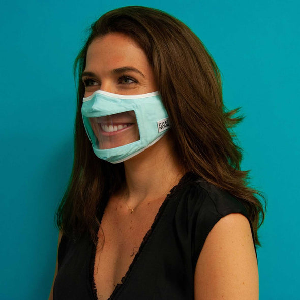 Side view of woman wearing Rafi Nova Adult Smile Mask Tie Behind in blue with white tie behind ear straps and standing against blue background.