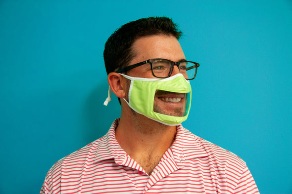 Photo of model wearing smile mask in green with white straps posing against blue background.