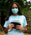 Photo of girl outside in backyard holding Rafi  Nova mask case in solid black with rainbow Hmong textile. Mask contains everyday masks is purple, blue, green, grey, and yellow. Model wears blue everyday mask.