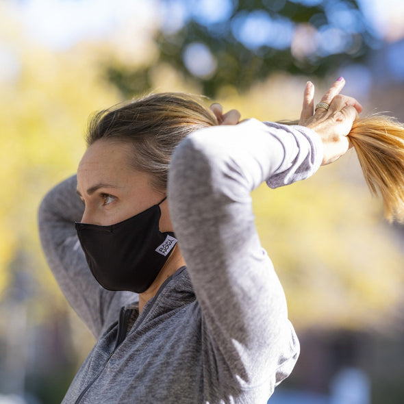 Photo of a female runner outdoors in the adult sized element mask in solid black with solid black ear loops, putting her hair into a ponytail.