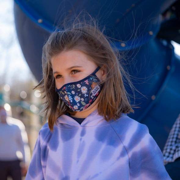Little girl, wearing a blue floral pattern little kids superfit mask with black ear loops.