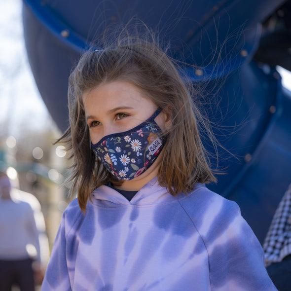 Little girl, wearing a blue floral pattern little kids superfit mask.