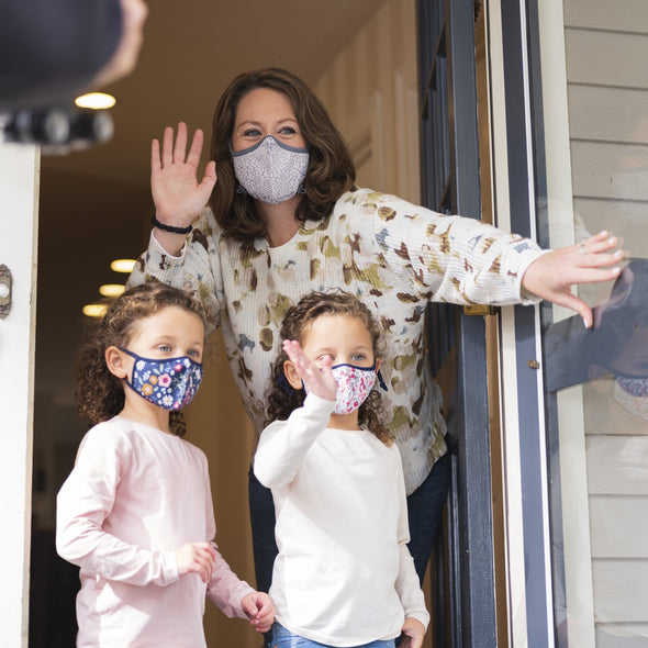 Photo of Mother wearing grey performance mask with two daughters wearing Little Kids SuperFIt masks, waving to postman from front porch.