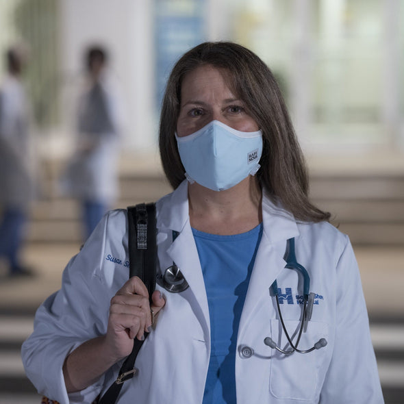 Photo of female nurse wearing a solid light blue adult sized performance mask with white ear straps and an adjustable chin toggle