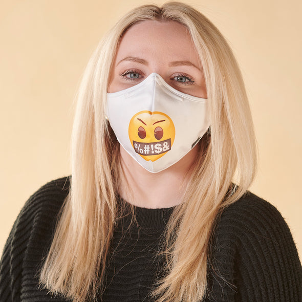 Woman wearing Rafi Nova x Emoji Adults Superfit mask in Expletive pattern. Woman standing against yellow background. White mask with round yellow face with markings covering face reading %#!$&. White adjustable ear straps.