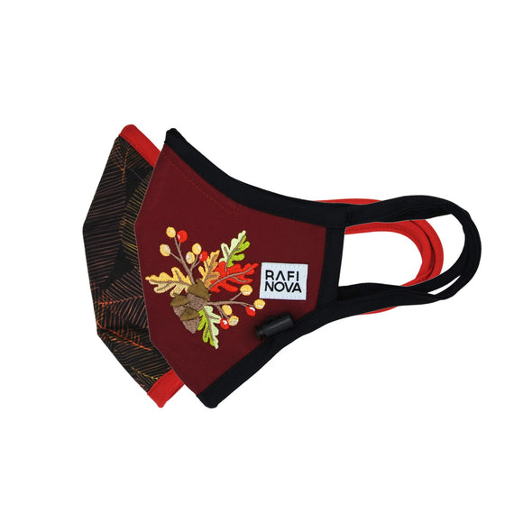 Side view of Adults Performance Mask 2-Pack Fall Leaves: 1 orange leaves pattern mask with crimson red ear loops and adjustable ear toggle and 1 crimson red mask with fall leaves decal and solid black ear loops and adjustable chin toggle.