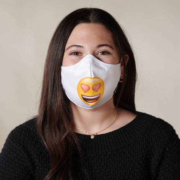 Photo of woman wearing Rafi Nova x emoji  Adults Superfit mask in heart eyes pattern. Round smiling yellow fave with red heart eyes against white background. White adjustable ear straps.