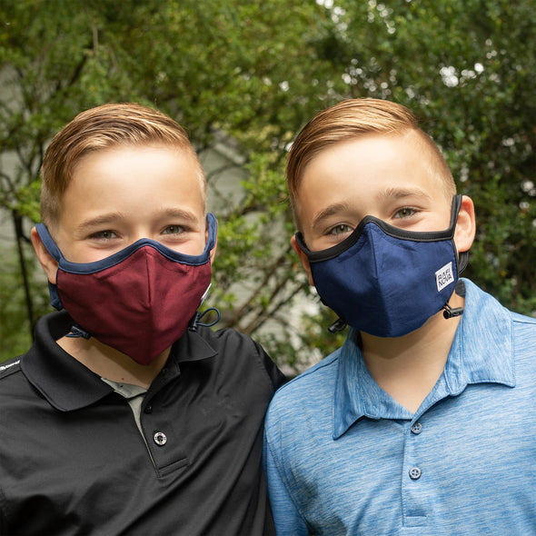 Image of two young teenage boys wearing Rafi Nova Teen Performance Masks: Left Mask is red with navy ear straps and adjustable chin toggle. Right mask is navy with solid black ear straps and adjustable chin toggle
