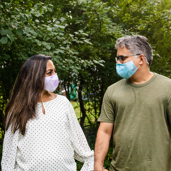 Man and woman wearing purple and blue tie dye masks holding hands and looking at eachother