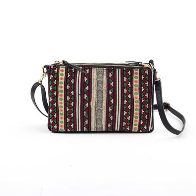 Side view of Rafi Nova Black Ha Giang Crossboy Bag. Black vegan leather bag. Red and Green patterned textile detailing on one side of bag made of recycled textiles made by Hmong artisans. Black detachable crossbody strap made of vegan leather.