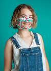 Photo of Model wearing Rafi Nova Adult Millie Smile Mask.  Adult Smile Mask in hand painted fabric pattern of pink flowers on blue and green background. White adjustable ear straps.