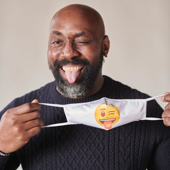 Man smiling and holding Rafi Nova x emoji superset mask in wink face. with white ear loops. Man stands against white background.