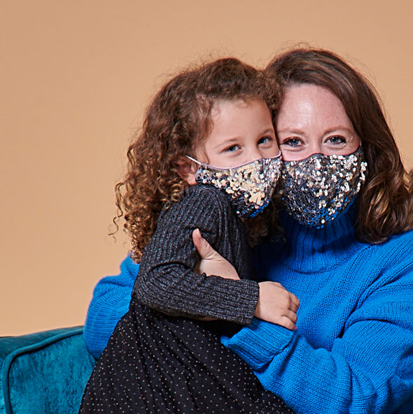 mother and daughter wearing matching silver sequin masks