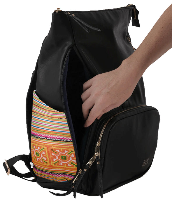 Hand reaching into Rafi Nova Black Sapa Supernova  Backpack. Black Vegan leather bag with fabric detailing of textiles made by Hmong artisans. Side pocket for easy access to bags interior.