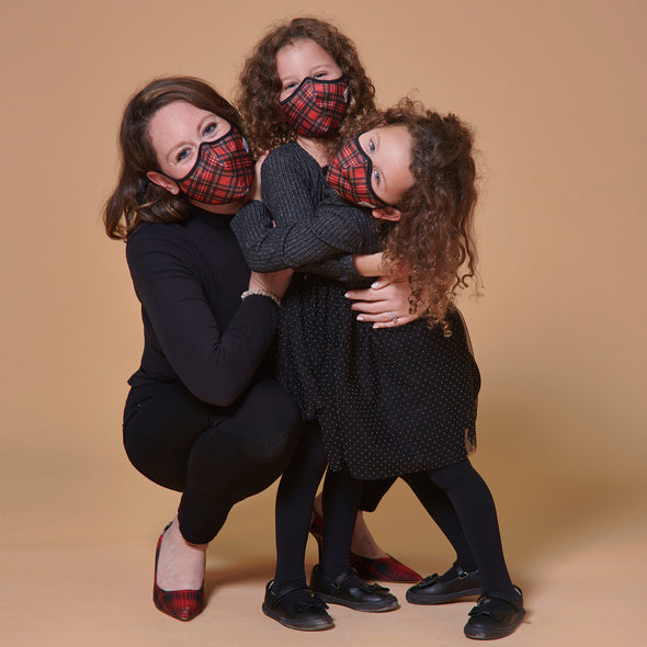 Mother and two daughters wearing matching red Tartan pattern superfit masks.