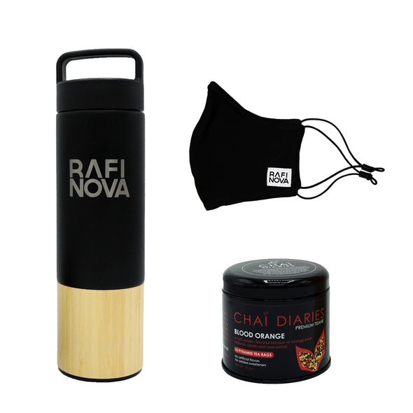 Front view of Rafi Nova x Welly Water Traveler Bottle, Tea, and Element Mask Set. One Black Water Bottle with a bamboo base, with Rafi Nova logo printed in silver. Side view of One black element mask with black adjustable ear loops. Side view of Chai Diaries tea with champagne raspberry.