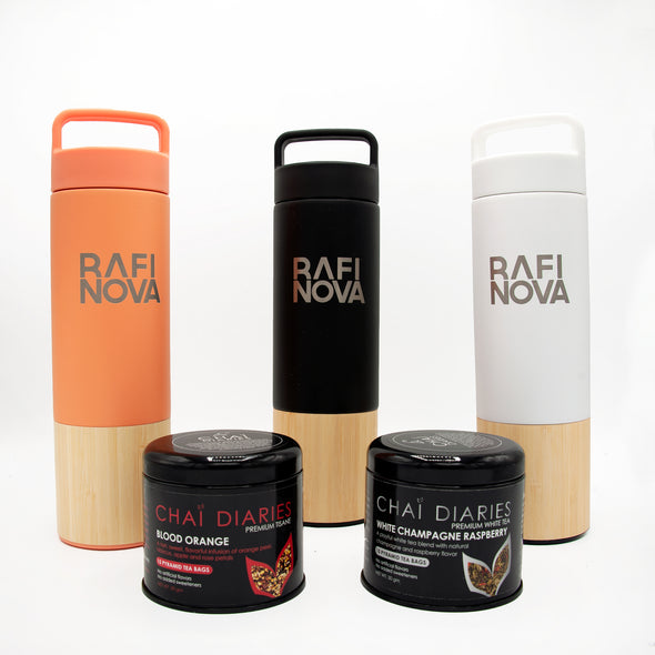Front view of Rafi Nova x Welly bottles with tea packages. One coral colored water bottle with bamboo lining on bottom and grey printed Rafi Nova logo. One black colored water bottle with bamboo lining on bottom and grey printed Rafi Nova logo. One white colored water bottle with bamboo lining on bottom and grey printed Rafi Nova logo. Two packages of tea , one blood orange flavored and one white champagne raspberry flavored.