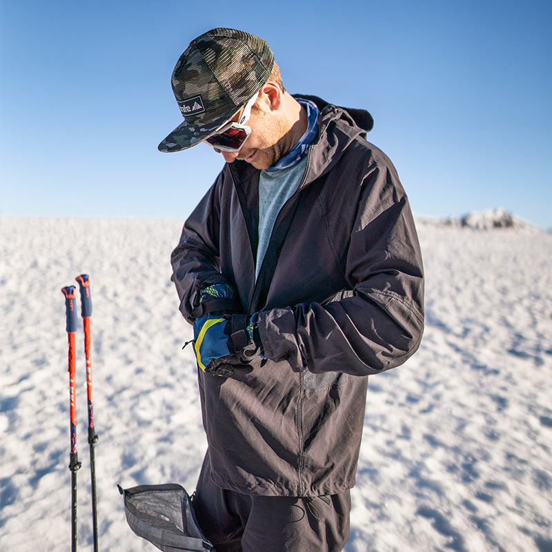 skier checks his pockets in the black recon pullover on independence pass
