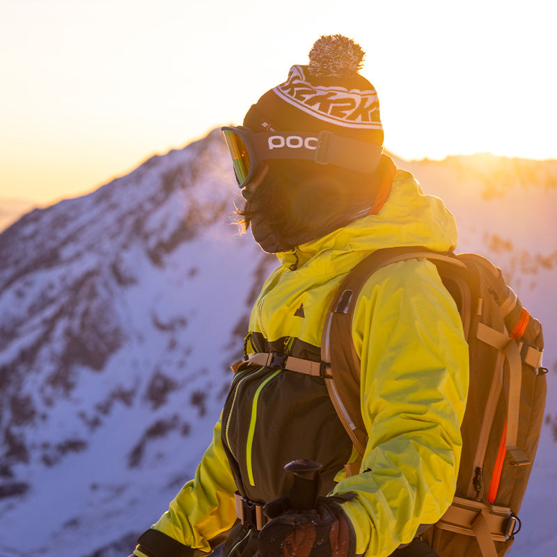 skier at sunset in lime pyramid jacket