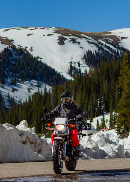 Snowboarder riding motorcycle up to Independence Pass